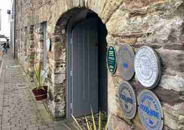 Stone front of Tannery Restaurant with 5 awards on the wall.