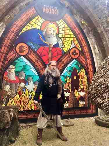 Man dressed as Viking standing in front of colourful stained glass window.
