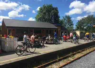 lots of cyclists on a train platform, sunny day.