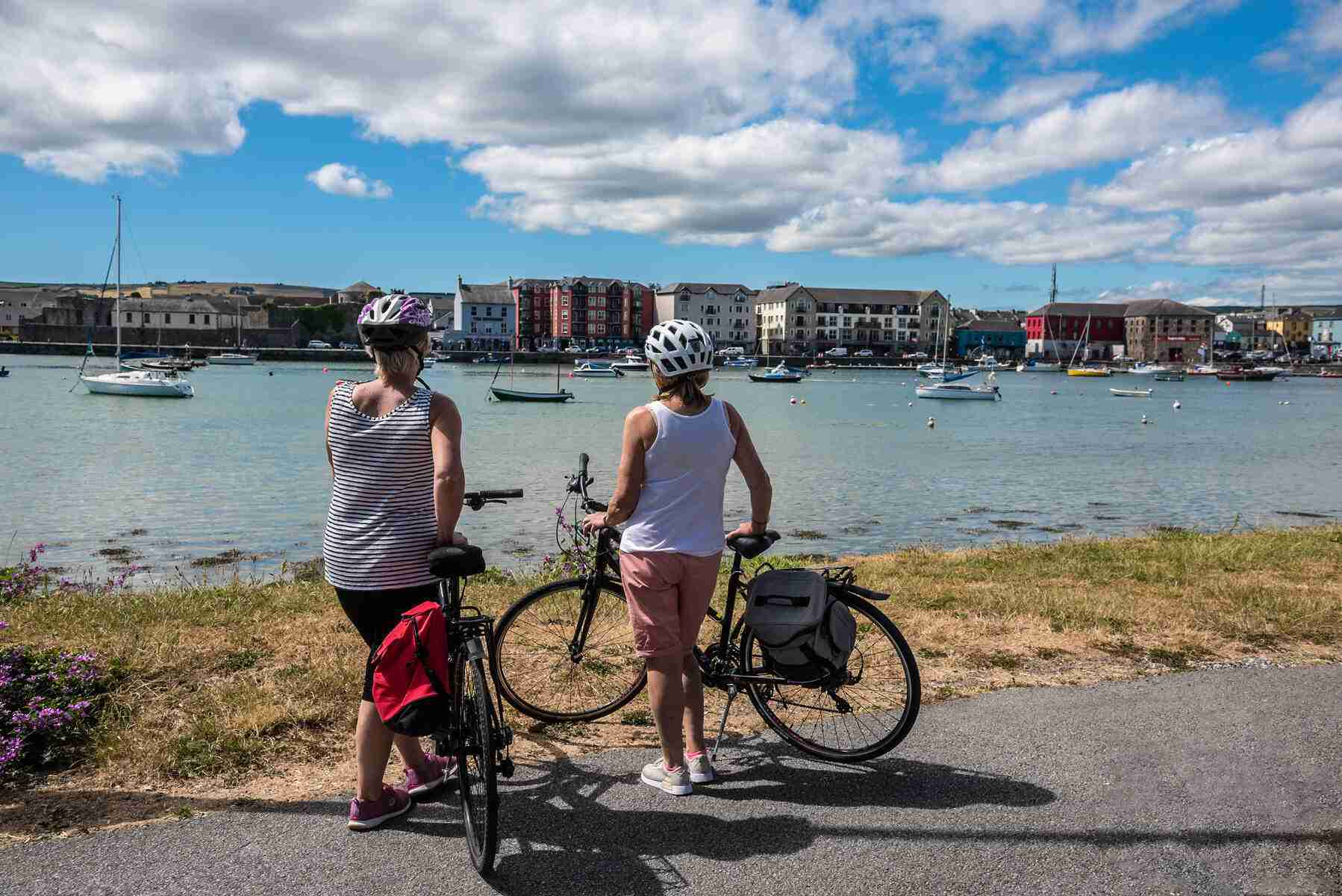 Two women standing with their bikes at the beginning of Waterford Greenway on the southern bank of the River Suir in Waterford City