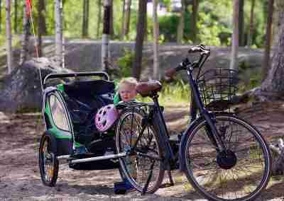 child standing beside adult bike and child's town-along with pink helmet in hand.