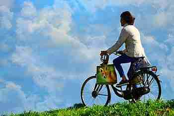 woman cycling in the countryside with blue sky in the background