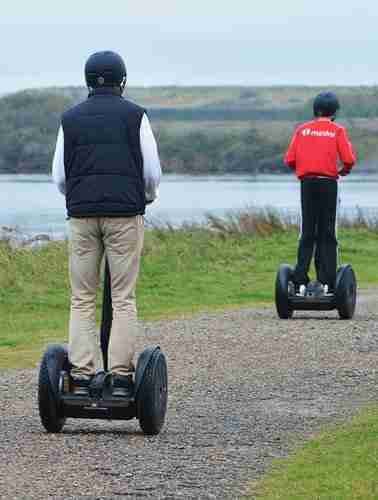 father & son on segways on gravel path with sea and hills in the background.