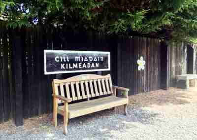 Bench on railway platform with sign for 'Kilmeadan' on the wooden fence behind it.